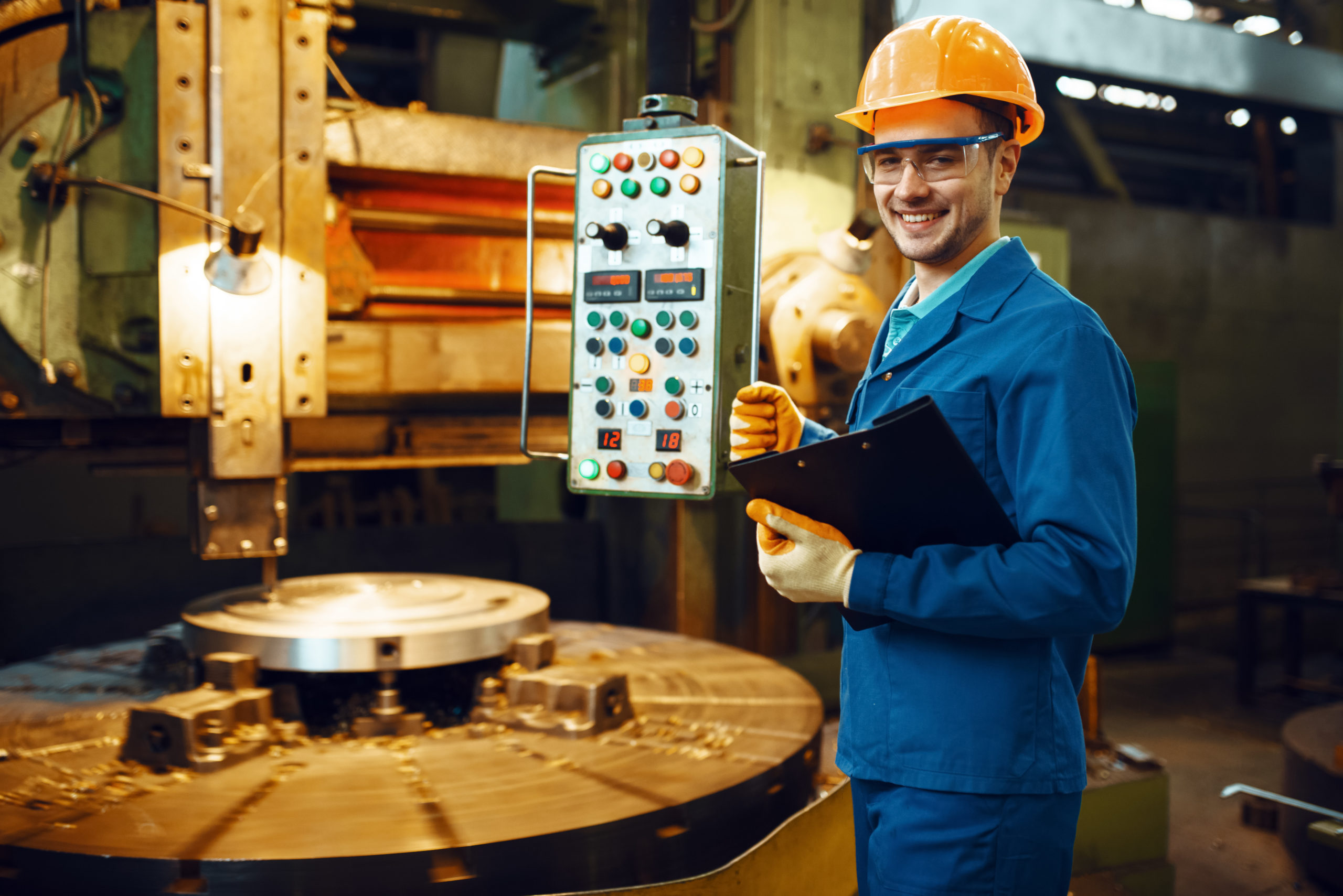 Turner in uniform and helmet stanging at the automated lathe, factory. Industrial production, metalwork engineering, power machines manufacturing